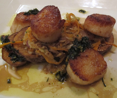 Pan Seared Scallops with sauteed carrots and cabbage, confit potato, white bean puree and pesto garnish.