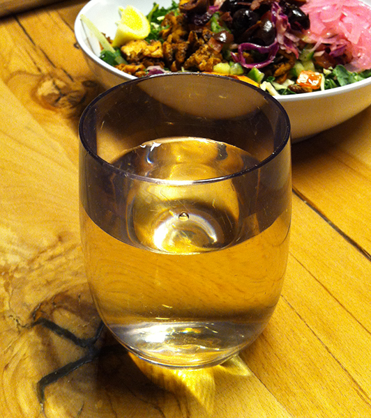 Glass of white wine with salad bowl